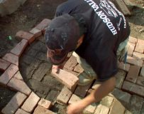 A contractor lays pavers for the sidewalk.